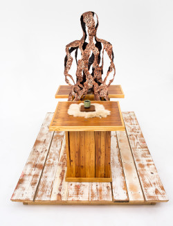 copper sculpture sitting at reclaimed wooden table and bench