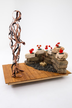 lifesize sculpture looking at carved wooden cross and origami flowers